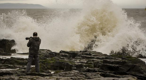A man photographs waves on Porthcawl Beach in South Wales
