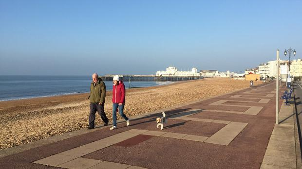 A couple walk their dog in the sunshine in Southsea, Hampshire, as the good Easter weather continues across the UK