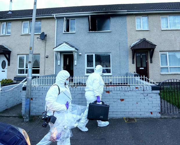 PSNI forensic officers attend the scene of the arson attack at Malvern Way in Belfast