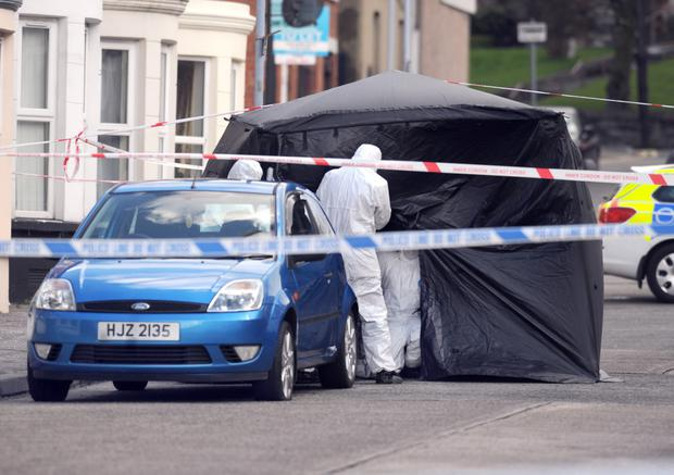 Police forensics officers examine the car in which the body of a man was discovered in Windsor Road, south Belfast, yesterday