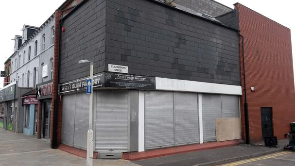 Shutters shield the damage to a beauty salon owned by a Polish woman that was set on fire in Belfast