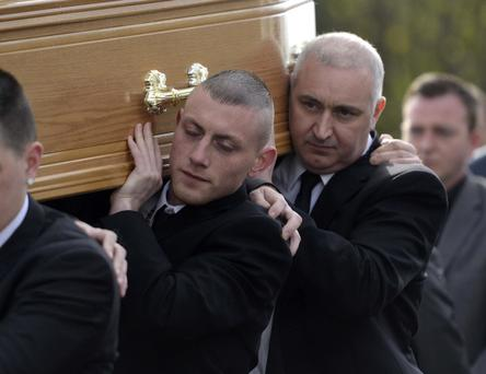 Kyle Neil's twin brother Irwin (left) carries his coffin