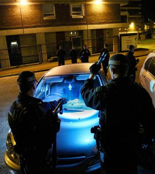 Police officers examine the car that was damaged by shrapnel in the Victoria Parade area of north Belfast on Tuesday night
