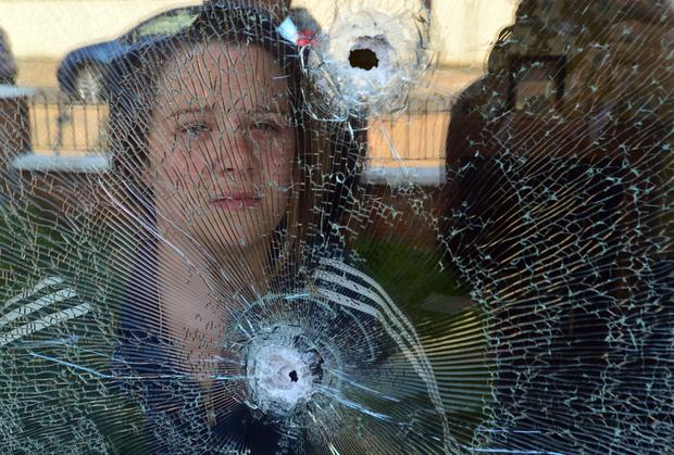Saoirse Conlon yesterday at the shattered window of her home in Norglen Drive in west Belfast