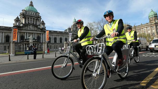 Regional Development Minister Danny Kennedy, left, Belfast Lord Mayor, Councillor Arder Carson and Frank O'Donnell, general manager of Coca-Cola in Ireland and Northern Ireland, try out Belfast's new bike hire scheme