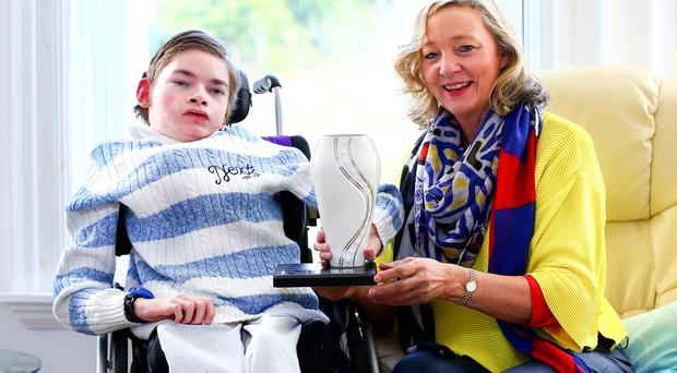Joyce Craig, who was voted Belfast Telegraph Mum of the Year, at home with her trophy and son Christopher