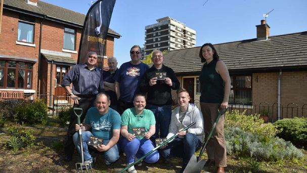 Members of the New Lodge Grow Wild community group in the garden they are set to make over