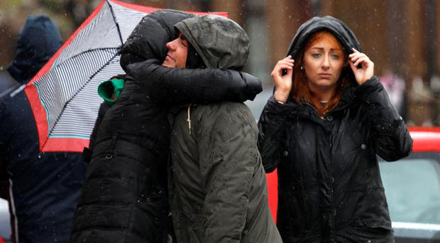 Shocked residents gather in the rain at the scene of the murder of top republican Gerard 'Jock' Davison in Belfast yesterday