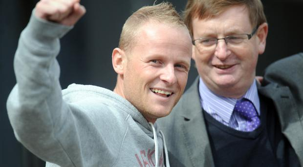 Loyalist Jamie Bryson punches the air as he leaves court yesterday, flanked by Willie Frazer