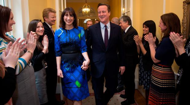 David Cameron and his wife Samantha are applauded by staff upon entering 10 Downing Street yesterday