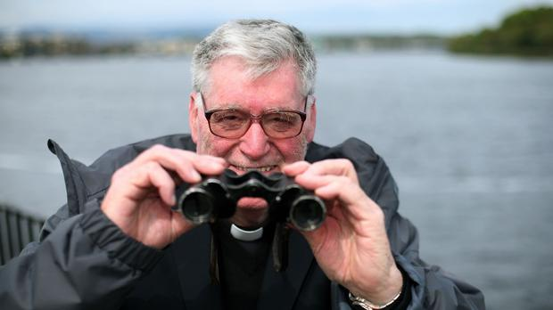 Fr Arthur O'Reilly holds a pair of binoculars taken from a surrendered German U-boat, which moored on the banks of the river Foyle, in Londonderry, following the end of the Second World War