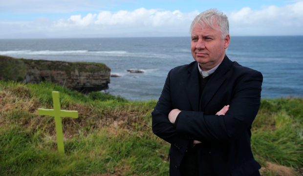 Parish priest Fr Christy McHugh stands by the cross in Mullaghmore which marks Lord Mountbatten's boat being blown up by the IRA in 1979