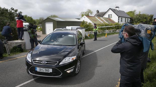 A coroner's car containing one of the bodies leaves a farmhouse in the townland of Boolaglass after a couple were found dead