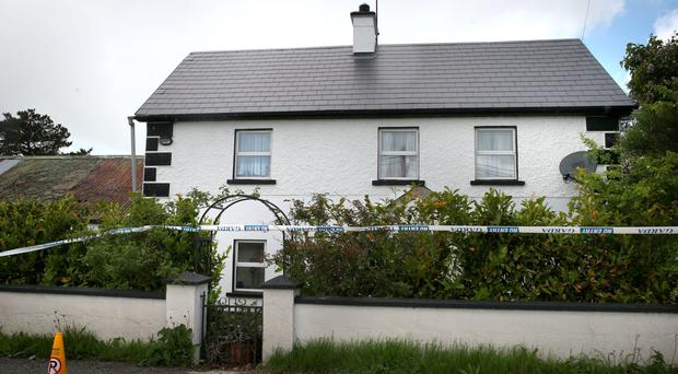 Police and forensics officers at the farmhouse in the townland of Boolaglass where the two bodies were discovered yesterday