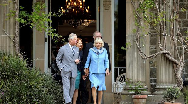 The Prince of Wales and Duchess of Cornwall emerge from the house to tour the Gardens at Mount Stewart House, in Co Down, on the last day of their visit to Northern Ireland