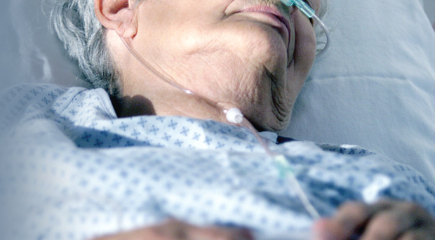 A woman lies in a hospital bed