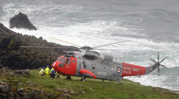 A Royal Navy helicopter from Prestwick in Scotland airlifts the casualty from Carrick-a-Rede