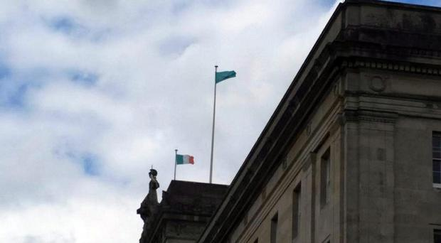 The Irish tricolour and another unsanctioned flag fly over Parliament Buildings at Stormont.