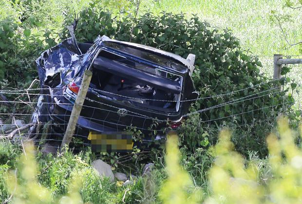 The wreckage of the car in which two people died lies in a hedge