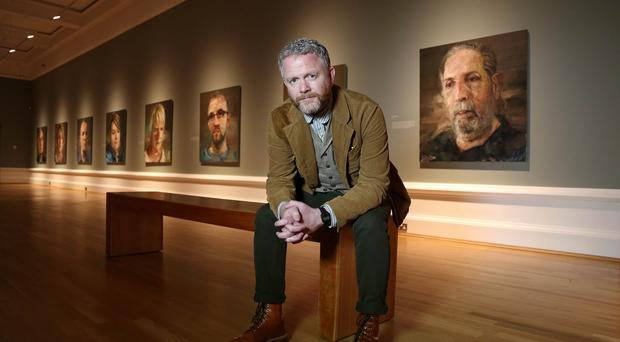 Colin Davidson in the Ulster Museum in Belfast with his portraits of 18 lesser known victims of the Troubles
