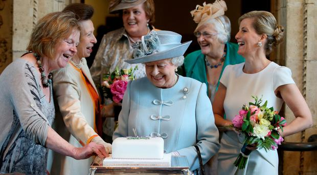 Sophie, Countess of Wessex, and Princess Anne look on in delight as the Queen cuts a Women's Institute Celebrating 100 Years cake at the centenary annual meeting of the National Federation Of Women's Institute at the Royal Albert Hall in London yesterday
