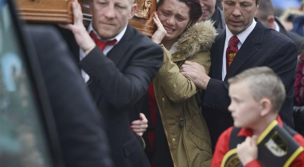 Racked by sorrow, Eamonn Magee jnr's sister Aine helps carry his coffin with her father Eamonn snr