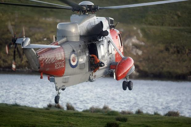 A Royal Navy Sea King helicopter takes part in the rescue operation at Fairhead in Co Antrim last night