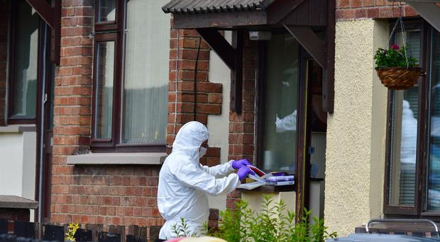 A forensic officer examines the victim's house yesterday