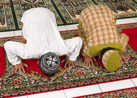 Two Muslims at prayer. Islam requires the faithful to pray five times a day