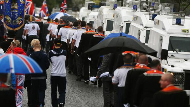 Police keep watch as an Orange Order parade makes its way down Woodvale Road next to the nationalist Ardoyne neighbourhood