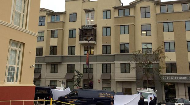 Police and officials stand outside of the Library Gardens apartment complex, where a fourth floor balcony rests on the balcony below after collapsing in Berkeley, California