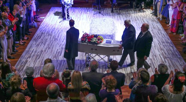 Mourners surround the stage as Peter Quigley's coffin arrives