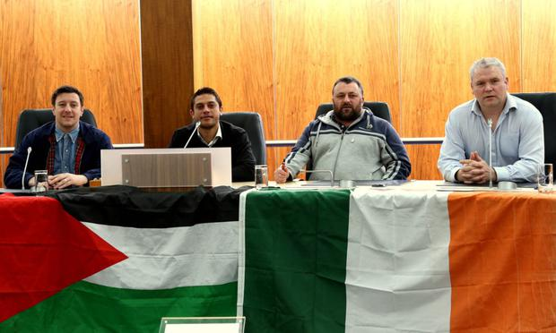 Councillors Darren O'Reilly, Gary Donnelly and Padraig McShane with Mohamed Al-Halabi (second left) and flags in council chamber