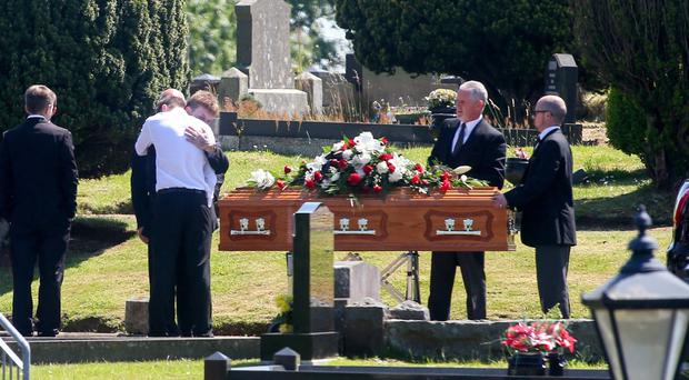 Friends comfort each other at the funeral of Ryan Mills at Christ Church in Derriaghy yesterday