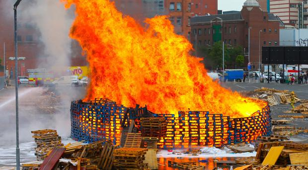Firefighters at the scene of the Sandy Row bonfire after it was set alight early yesterday