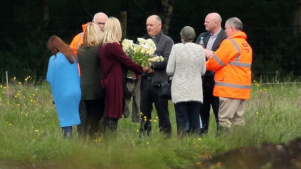 Local priest Father John O'Brien with members of Seamus Wright's family at the site in Coghalstown, Co Meath, where two bodies were discovered