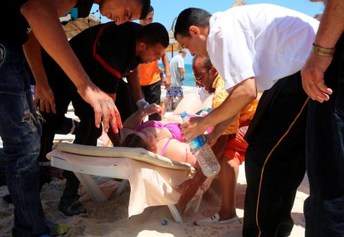 A woman is treated on the beach for gunshot wounds