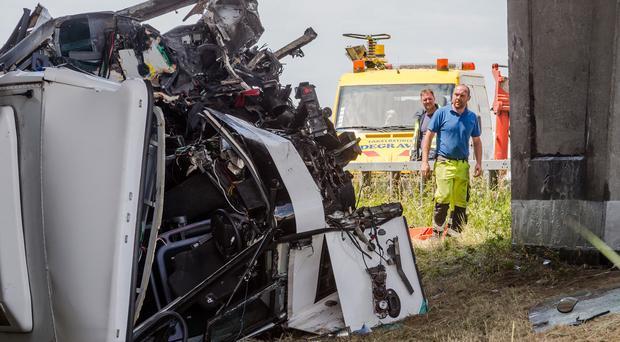 Safety workers attend to the bus which crashed on a motorway in Belgium