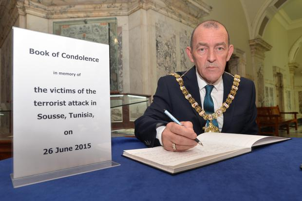 Belfast Lord Mayor Arder Carson signs the book of condolence for the victims of the massacre in Tunisia