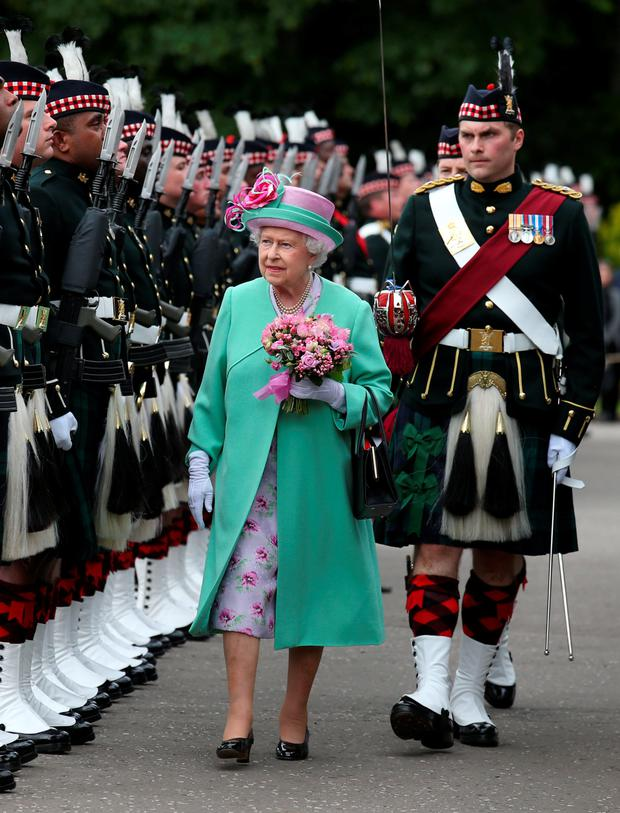 The Queen walks with guard commander Major Alastair Colville as they inspect a Guard of Honour from Fire Support Company, the Royal Highland Fusiliers, 2nd Battalion the Royal Regiment of Scotland, during the ancient Ceremony of the Keys at the Palace of Holyroodhouse, Edinburgh