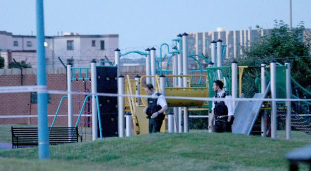Police and forensic officers examine the playpark in the Shankill area of Belfast last night after a shot was fired