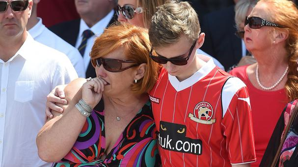 Suzie Evans is hugged by her son Owen Richards during a minute's silence in Walsall in memory of the victims of the Tunisia terror attack, including their relatives Patrick Evans, Adrian Evans and Joel Richards