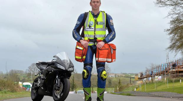 Dr John Hinds with his medical equipment and bike