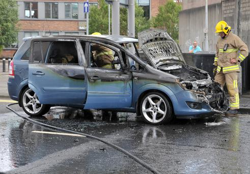 Firefighters at the scene of the car blaze at Dunbar Link In Belfast yesterday