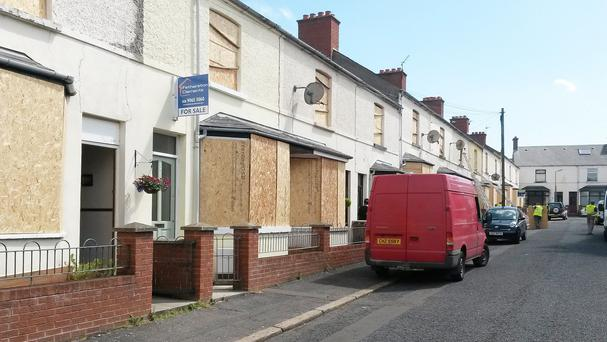 Terraced houses on Finvoy Street beside Comber Greenway in Belfast were boarded up in an effort to protect the properties
