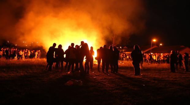 People stand near a small bonfire in the New Mossley area of Belfast as Loyalists prepare for the Twelfth of July marching season