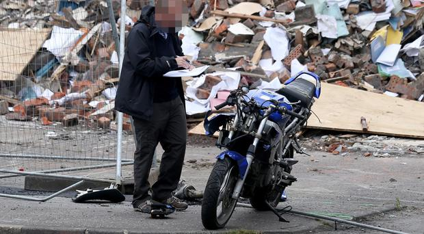 A police officer inspecting the motorbike at the scene on Fife Street in north Belfast where Eddie Hall died following a crash