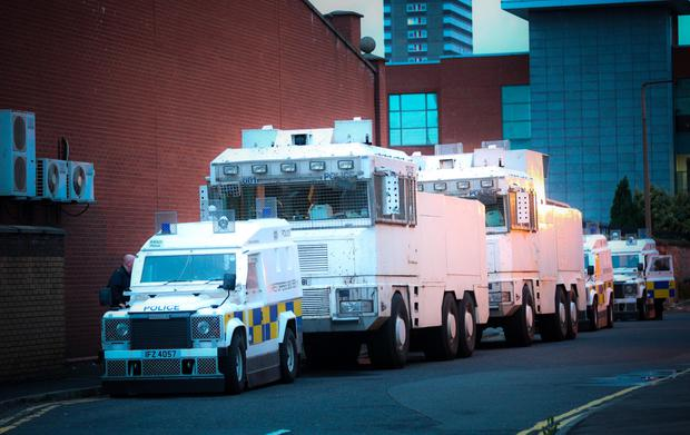 Police water cannons on standby at the Grosvenor Road Police Station in Belfast yesterday as Twelfth celebrations get under way