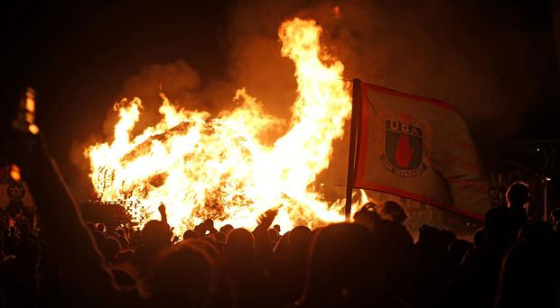 A UDA flag is seen near a bonfire in the Shankill area of Belfast