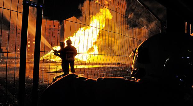 Firefighters tend to the blaze as members of the public shield their faces from the intense heat